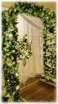 Wedding Archay wth pedestal flower arrangement underneat the archway