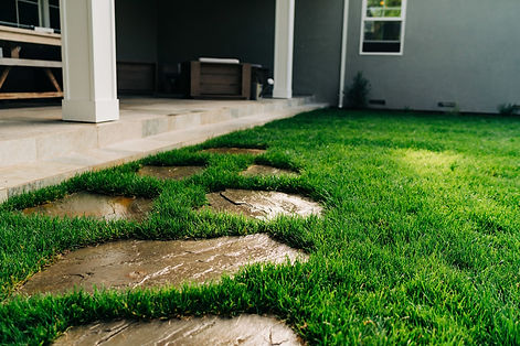 Stepping stones in the kid-friendly lawn lead to a porcelain tile patio.