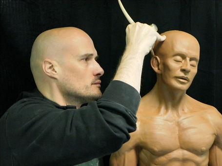 Enseignan conférencier Jean Sébastien Raud à l'oeuvre avec une sculpture en terre cuite