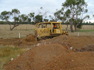 The bulldozer starts work levelling the heaps of dirt.