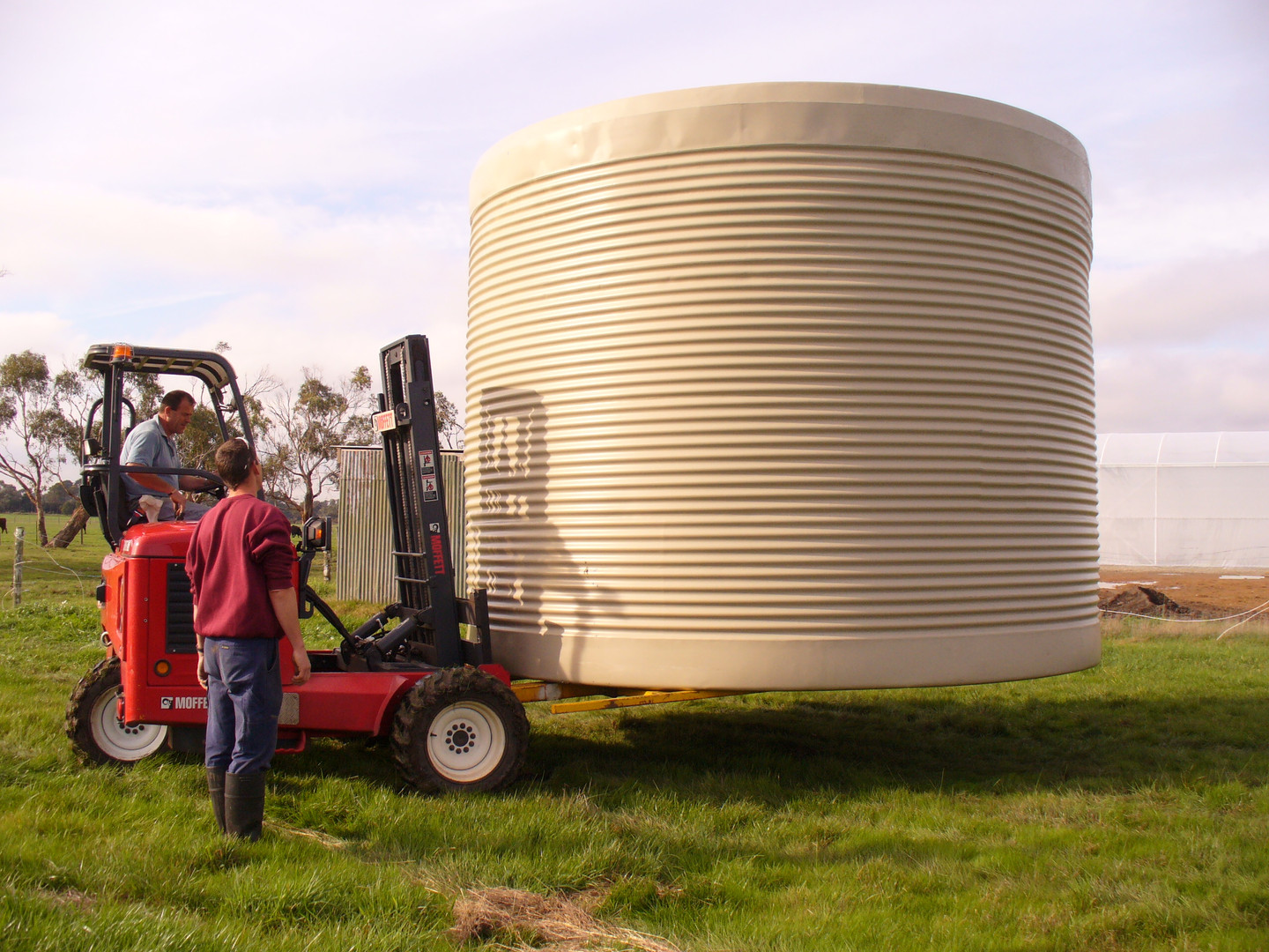 A 3 wheel - 4WD forklift moves the water tanks from the truck to their positon.