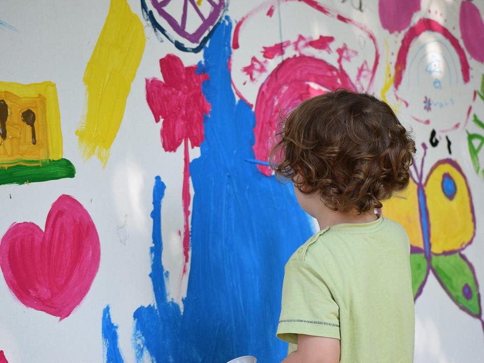Kinder malen auf der großen Wand.