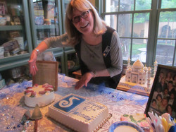 SI Davis member Phyllis Himmel gesturing at a sheet pan cake for the club's 65th Anniversary