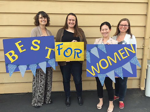 Smiling Soroptimists hold up a Best for Women banner