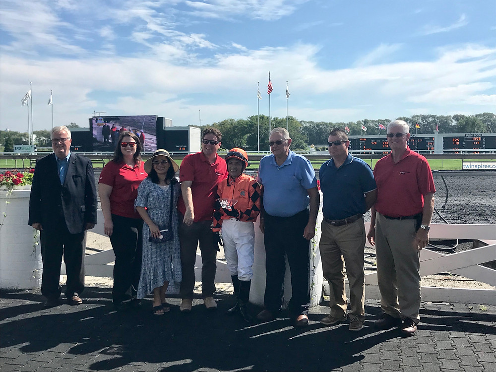 Pictured: Walker (left) presents an award to a winning jockey at the Arlington International Racecourse with members of the Crawford County, IL Farm Bureau