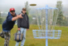 Disc golfer putting on a disc golf basket