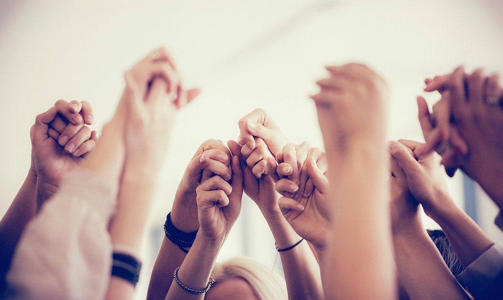 People in a group celebrating with their hands embraced in the air