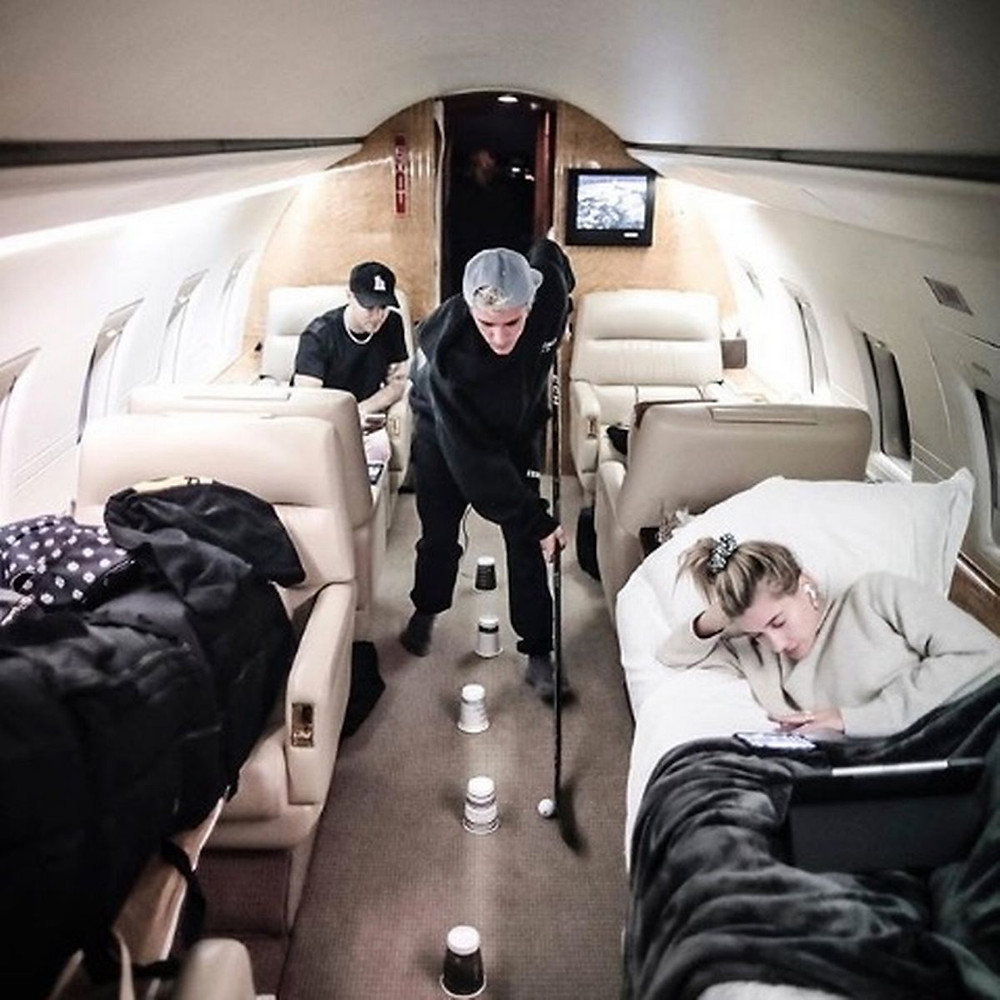 Justin Bieber playing hockey on a private jet.
