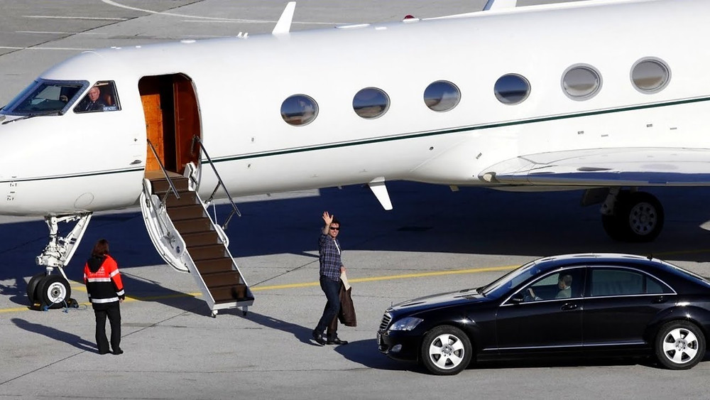 Tom Cruise waving beside his private jet.