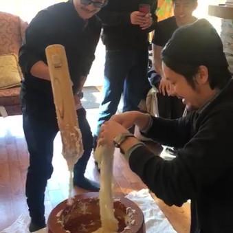 Men trying to prepare rice balls