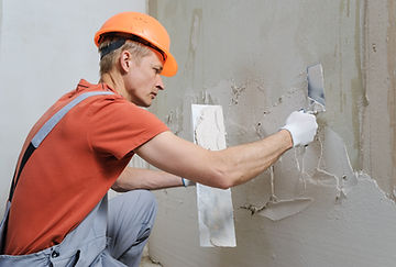 Worker is putting a gypsum plaster on a
