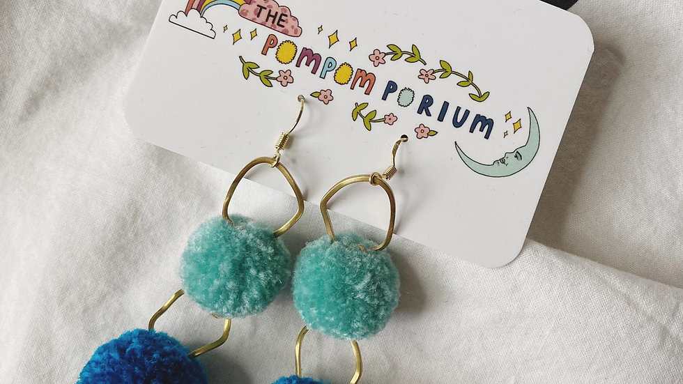 Two ombré blue poms with abstract gold connectors