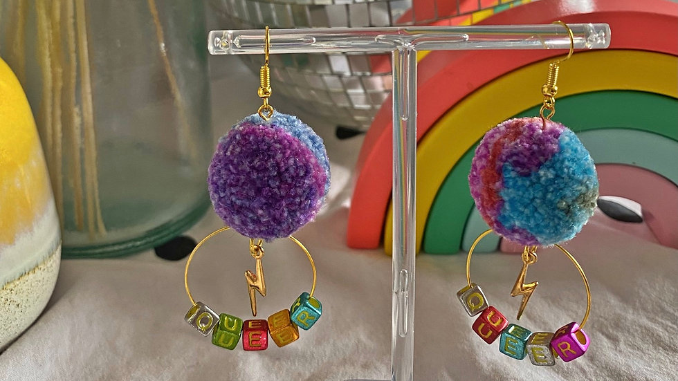 Purple and blue marbled pom poms with lightning charms and queer letter beads