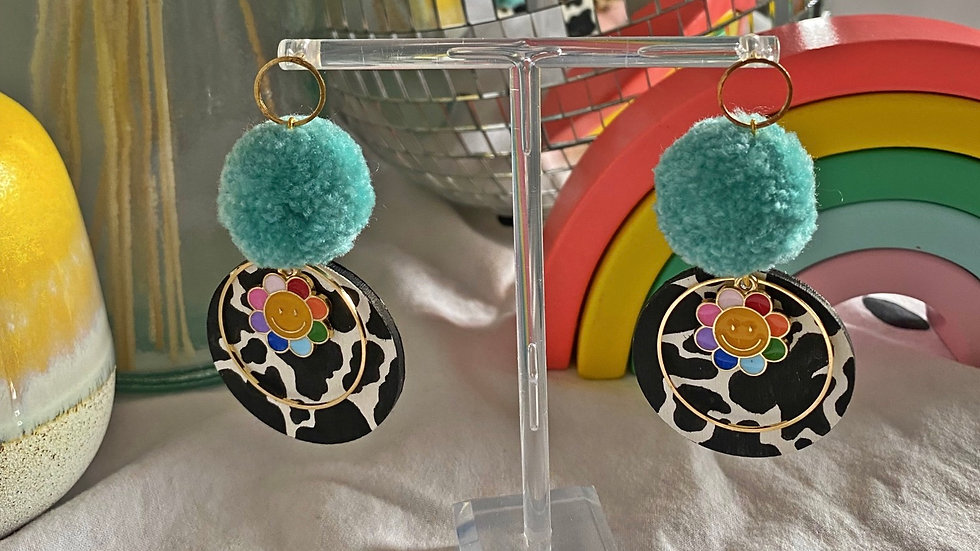 Bright blue pom pom earrings on circle connectors with hand painted cow print
