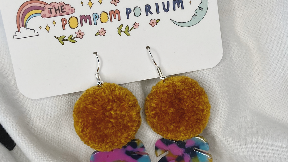 Mustard poms with tie dye acrylic charms in the shape of monstera leaves
