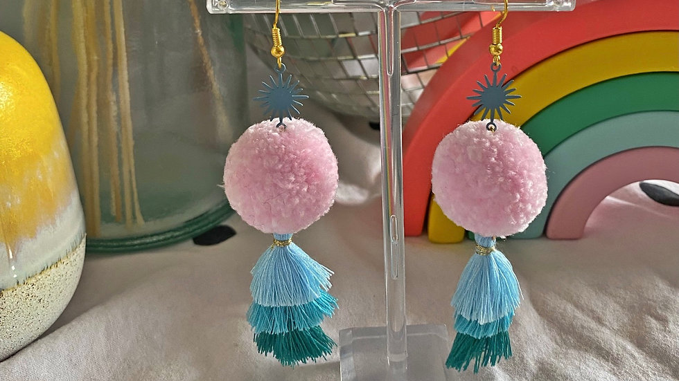 Pale pink pom pom earrings with sunburst charms and blue tiered tassels