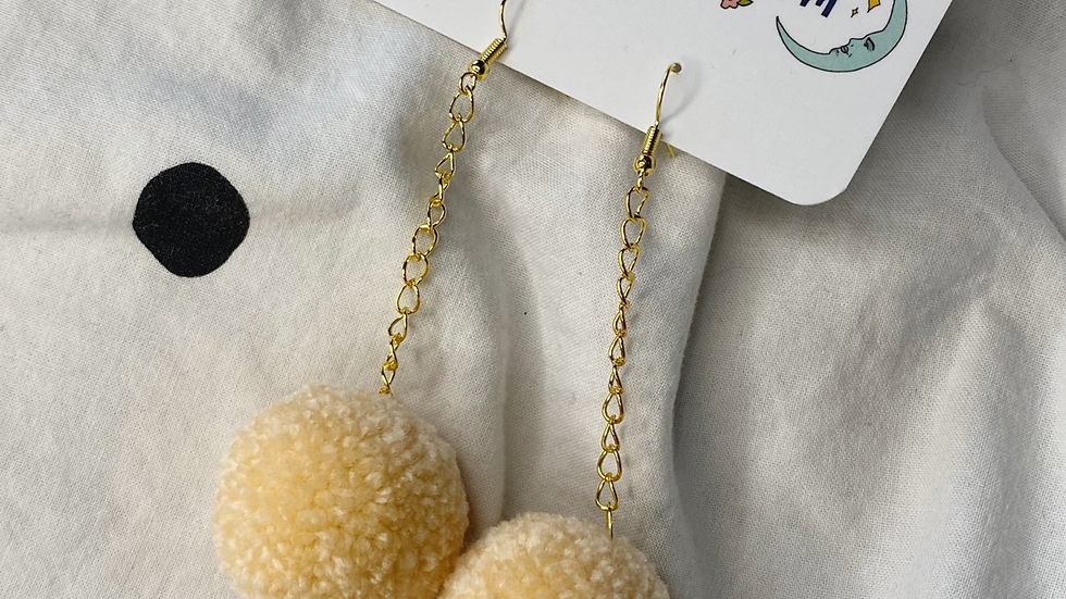 Creamy poms with rose charms on gold dangle chains