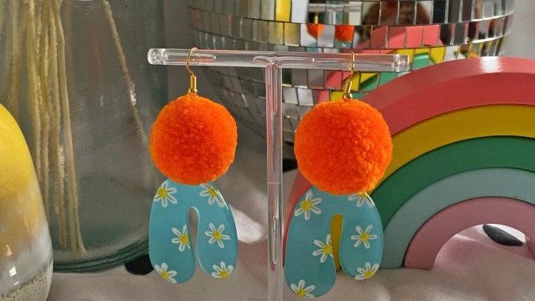 Neon orange pom pom earrings with daisy arch charms