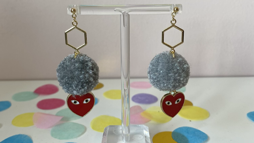 Grey poms with suspish heart charms, hanging on a hexagonal connector