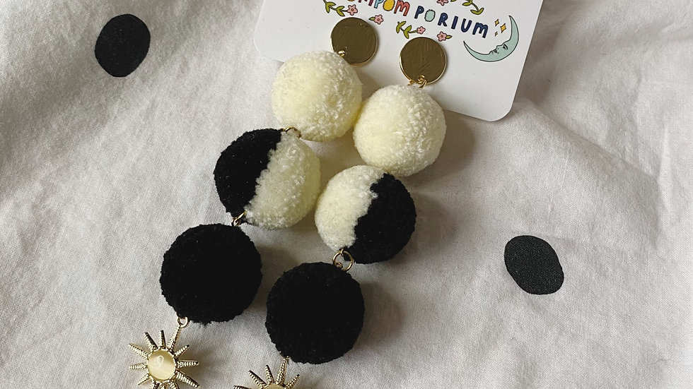 Moon phase inspired pom poms on circular studs, with purple cats eye star charms