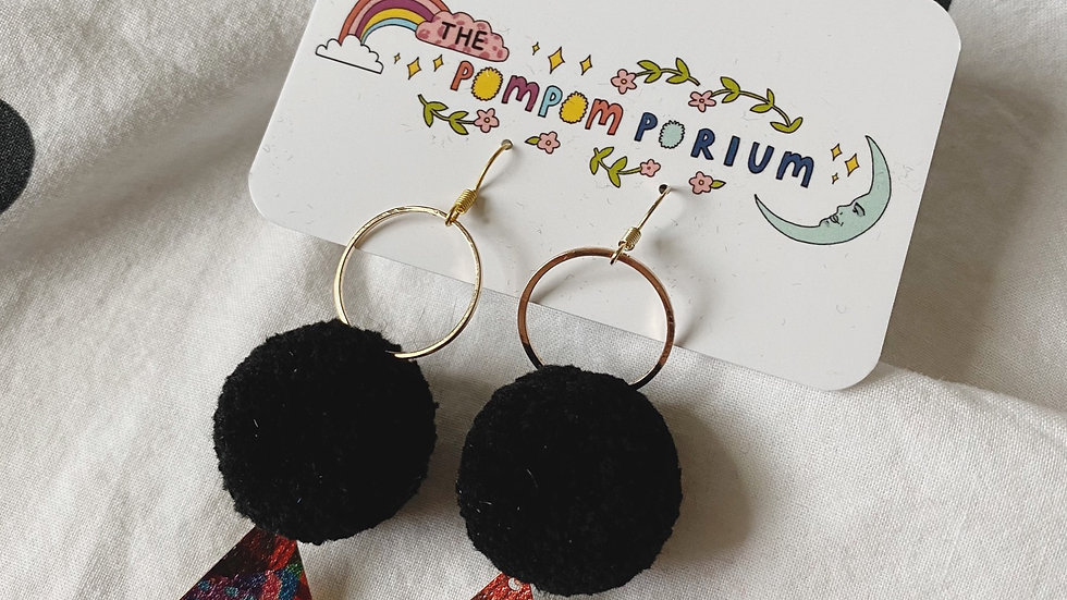 Circular connectors, black poms and abstract patterned triangle charms