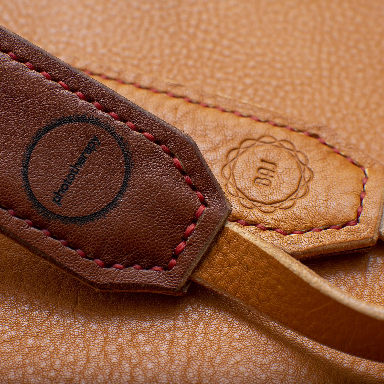 camera strap logo close up on tan