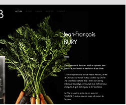A Wix website, showing half of the face of a French chef, and carrots and leaves on a black background