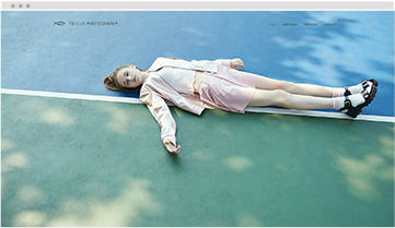 A Wix website of a photographer presenting one of their images of a young girl lying on the ground