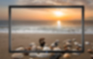 led tv screen showing seascape and sunrise with beach
