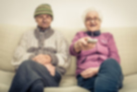 old couple on sofa with tv remote watching flat screen tv
