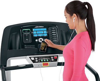 Woman onnecting iphone to Life Fitness E3 elliptical crosstrainer console