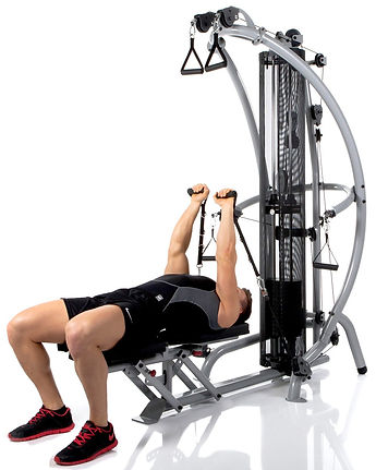 Inspire M1 Gym with seat in flat position with male model performing pec flys