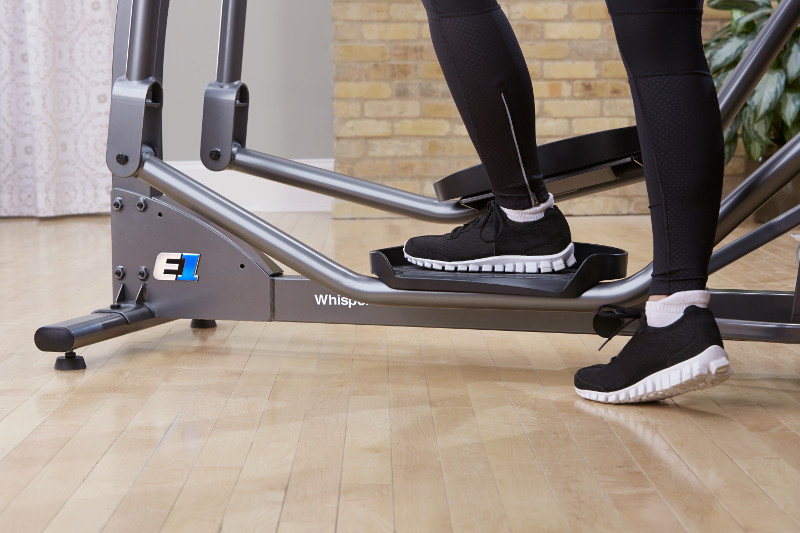 Person mounting Life Fitness E1 elliptical crosstrainer in room setting