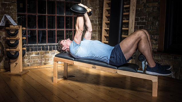 Nohrd Tri Trainer bench with male model lying on it using Swing Weights