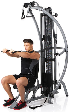 Inspire M1 Gym with seat in upright position showing male model performing bench press