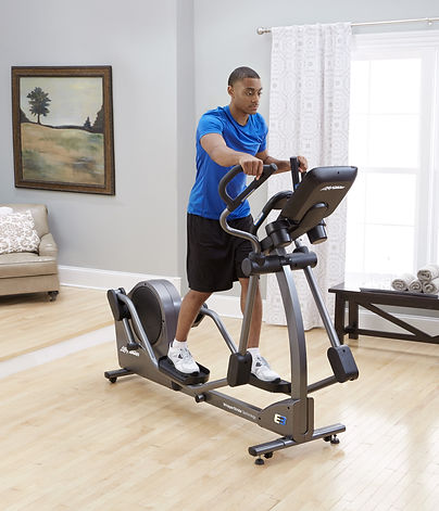 Man using Life Fitness E3 elliptical crosstrainer in room