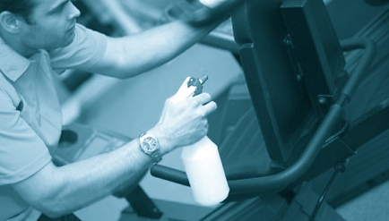 Service engineer cleaning fitness equipment