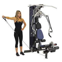 Inspire M2 home gym with woman doing lateral raises