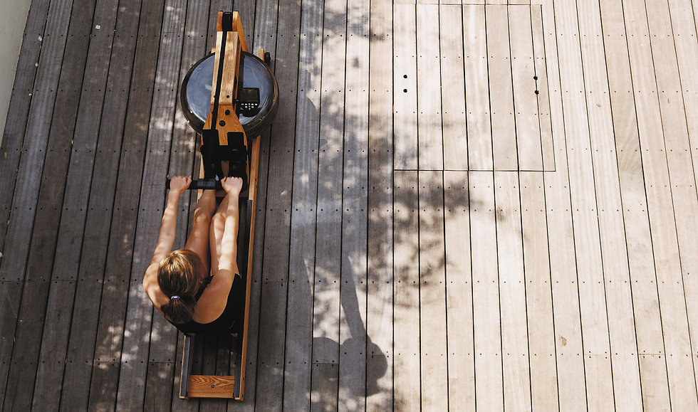 WaterRower being used by female model outside on wooden decking