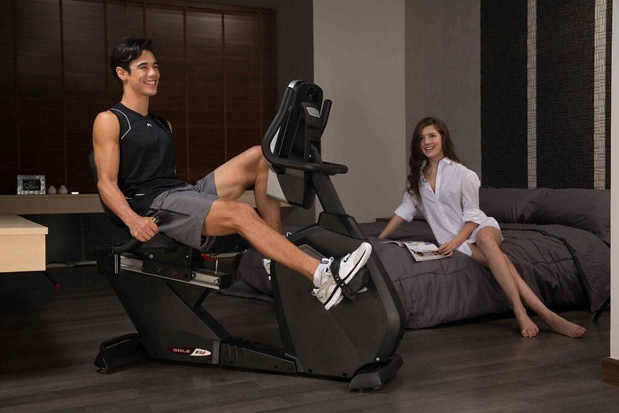 Sole R92 Recumbent Bike with male model and female looking on from Sofa