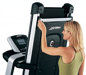 Woman holding release lever on the Life Fitness F3 treadmill folding mechanism