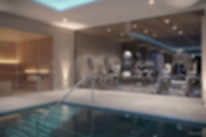 Fitness equipment in glass room at the side of swimming pool in basement