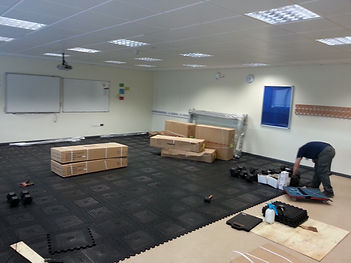 Showing Fitness Options engineers at Maesteg School laying the specialist protective rubber flooring prior to installation of fitness equipment