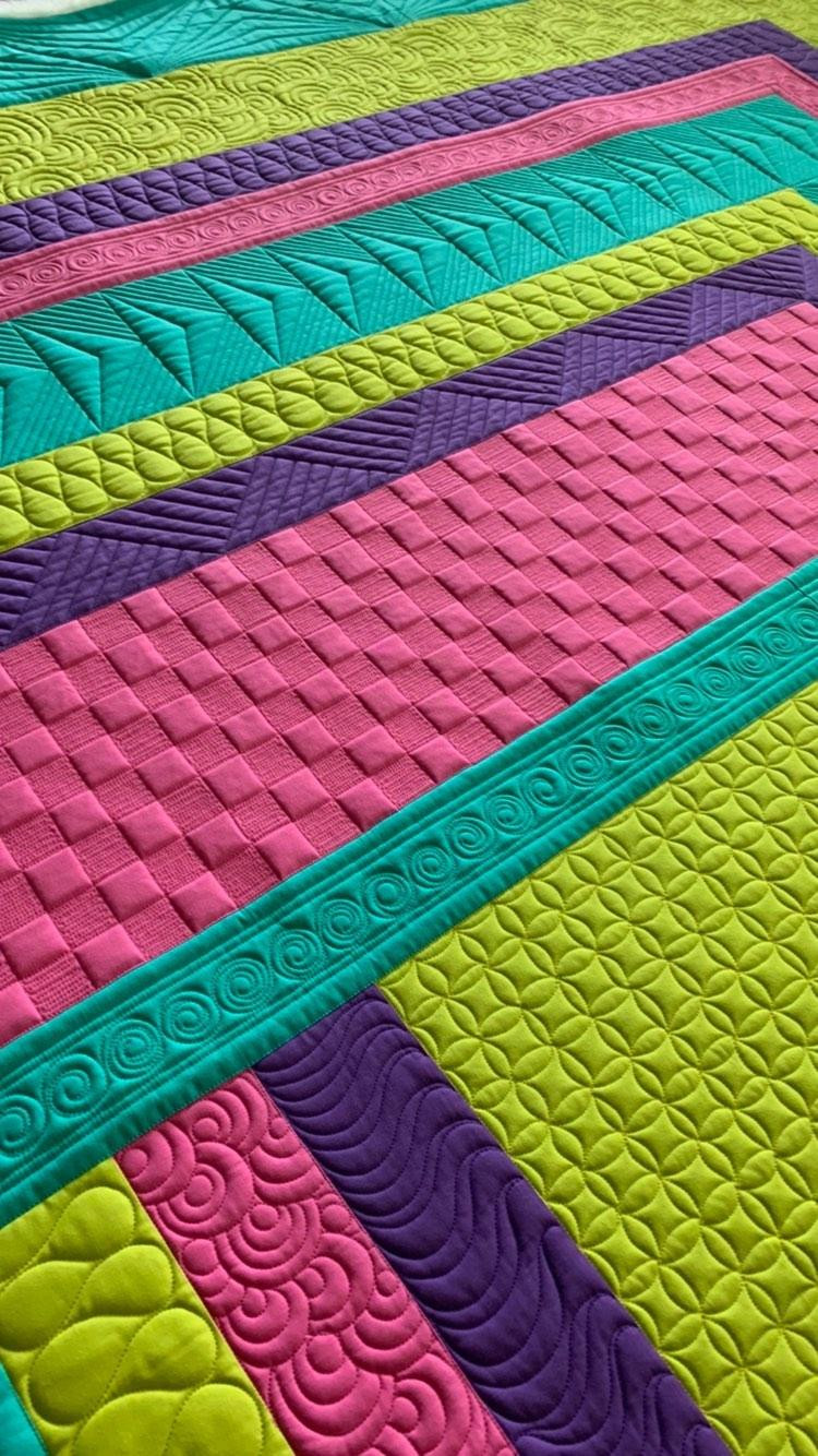 Texture on a quilt created with swirls, dense lines and ribbon candy