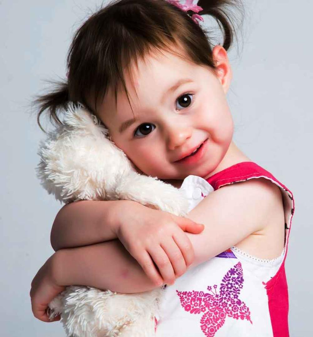 Hispanic toddler, girl, holding a stuffed animal