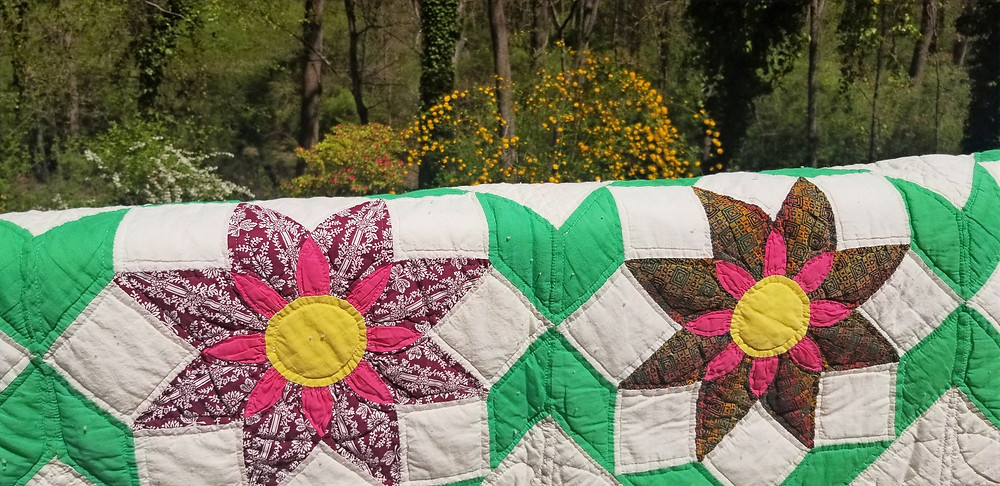A large handmade quilt on the railing of a deck
