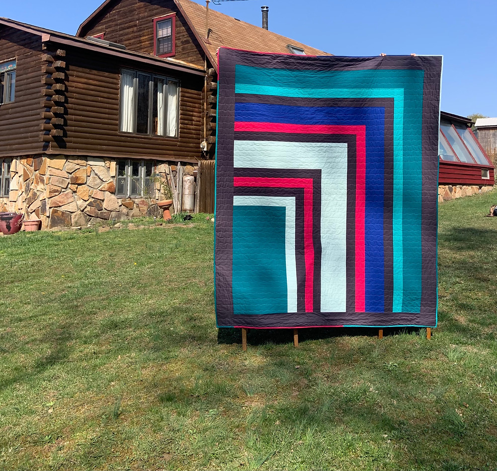 A Mod Cabin quilt in front of an older log cabin style home
