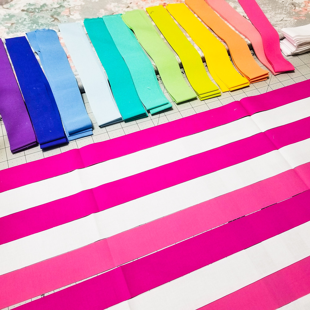 fabric cut into strips for quilt piecing in rainbow order