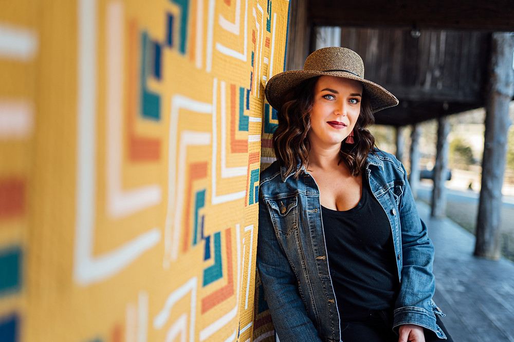 Attractive woman wearing a hat standing near mustard yellow quilt