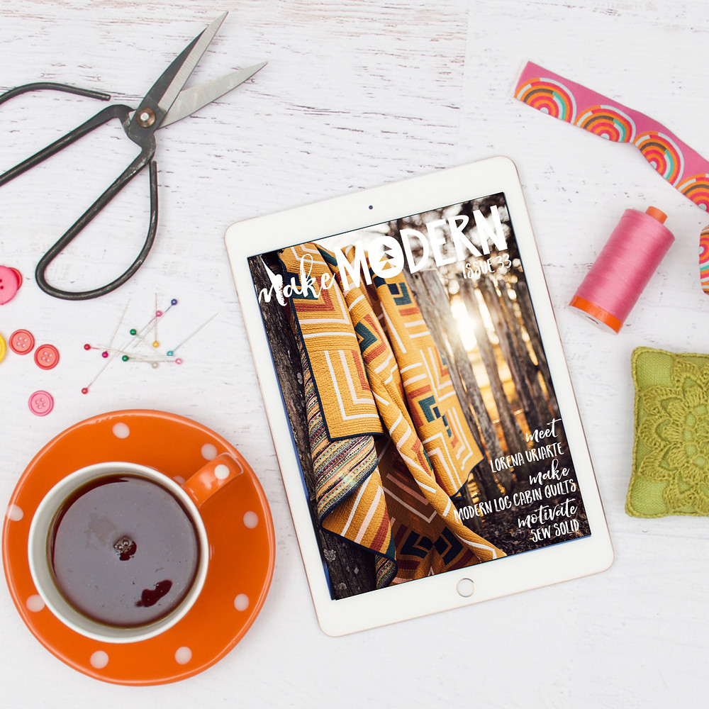 flatlay of tablet displaying digital magazine, mug of coffee sewing notions